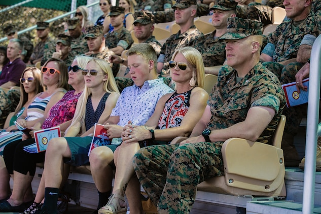 Lt. Col. Erick T. Clark, off-going commanding officer, 1st Battalion, 7th Marine Regiment, sits with his family during the unit's change of command ceremony aboard the Marine Corps Air Ground Combat Center, Twentynine Palms, Calif., June 4, 2018. The change of command ceremony ensures that the unit and its Marines are never without official leadership, and also signifies an allegiance of Marines to their unit's commander. (U.S. Marine Corps photo by Lance Cpl. Rachel K. Porter)
