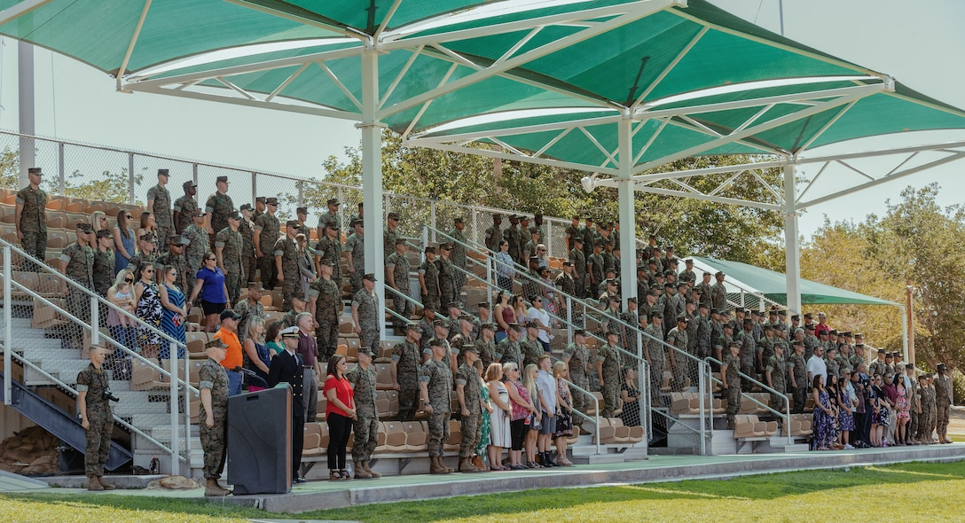 The audience stands for the Marines Hymn during 1st Battalion, 7th Marine Regiment's change of command ceremony aboard the Marine Corps Air Ground Combat Center, Twentynine Palms, Calif., June 4, 2018. The change of command ceremony ensures that the unit and its Marines are never without official leadership, and also signifies an allegiance of Marines to their unit's commander. (U.S. Marine Corps photo by Lance Cpl. Rachel K. Porter)