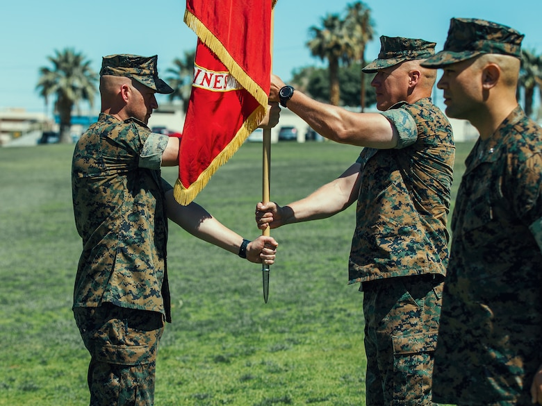 Sgt. Maj. Brian E. Anderson, sergeant major, 1st Battalion, 7th Marine Regiment, passes the battalion colors to Lt. Col. Erick T. Clark, off-going commanding officer, 1st Battalion, 7th Marine Regiment, during the unit's change of command ceremony aboard the Marine Corps Air Ground Combat Center, Twentynine Palms, Calif., June 4, 2018. The exchange of colors, from an outgoing commander to an incoming one, is the crowning moment of the ceremony and ensures that the unit and its Marines are never without official leadership and also promotes a continuation of trust. (U.S. Marine Corps photo by Lance Cpl. Rachel K. Porter)