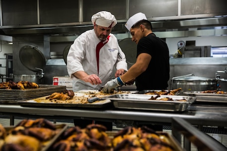 Food service specialists prepare chicken for the Phelps Mess Hall grand re-opening aboard the Marine Corps Air Ground Combat Center, Twentynine Palms, Calif., June 4, 2018.  Phelps Hall has been closed since November 11, 2017, due to renovations to improve the efficiency of the facility. (U.S. Marine Corps photo by Lance Cpl. Margaret Gale)