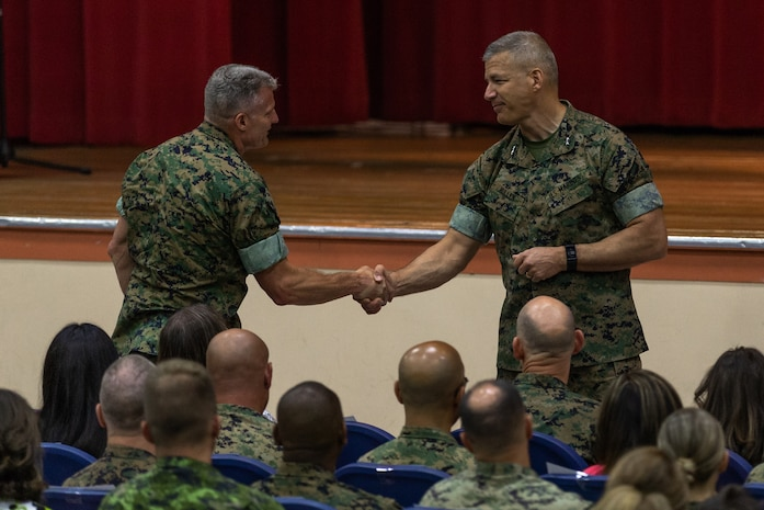 Maj. Gen. William F. Mullen III, off-going commanding general, Marine Corps Air Ground Combat Center, shakes hands with Brig. Gen. Roger Turner, on-coming commanding general, MCAGCC, between speeches during the installation's change of command ceremony aboard the Combat Center, Twentynine Palms, Calif., June 8, 2018. The change of command ceremony ensures that the unit and its Marines are never without official leadership, and also signifies an allegiance of Marines to their unit commander. (U.S. Marine Corps photo by Lance Cpl. Rachel K. Porter)