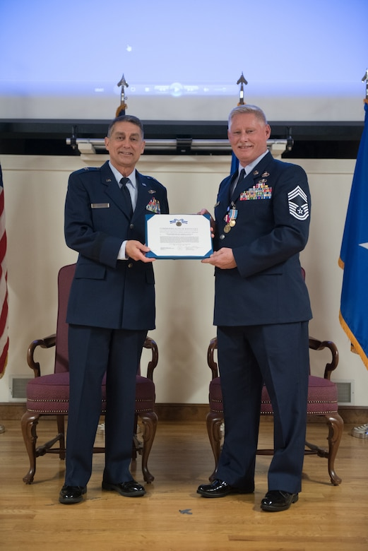Brig. Gen. Warren Hurst (left), Kentucky's assistant adjutant general for Air, presents the Kentucky Distinguished Service Medal to Chief Master Sgt. Joseph E. Atwell Jr. during Atwell's retirement ceremony at the Kentucky Air National Guard Base in Louisville, Ky., April 15, 2018. Atwell's career spanned more than 30 years in both the active-duty Air Force and Kentucky Air National Guard. (U.S. Air National Guard photo by Master Sgt. Vicky Spesard)