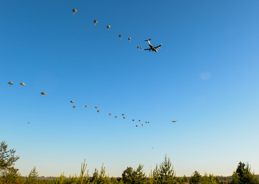 82nd Airborne Paratroopers jump from U.S. Air Force C-17 Globemasters over a drop zone in Adazi, Latvia, June 9, 2018. Four aircraft from the 62nd Airlift Wing at Joint Base Lewis-McChord, Washington and four aircraft from the 437th Airlift Wing at Joint Base Charleston, South Carolina provided support to exercise Swift Response 18. Swift Response included approximately 2,300 participants from seven allied nations to help train the U.S. Global Response Force, led by the U.S. Army's 82nd Airborne Division, in Joint Forcible Entry operations. (U.S. Air Force photo by Staff Sgt. Jimmie D. Pike)