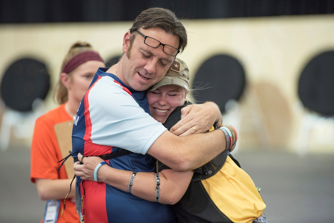 DoD Warrior Games archery competitors hug.