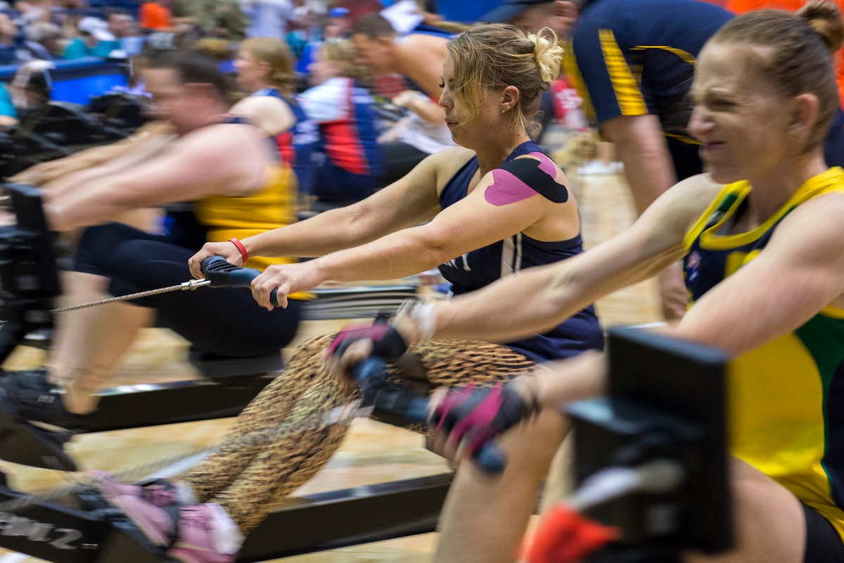 Athletes on indoor rowing machines compete in a gym.
