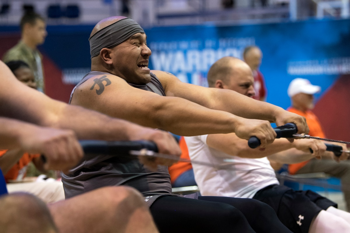 A sailor winces while pulling the handle of a rowing machine, alongside fellow competitors doing the same in a gym.
