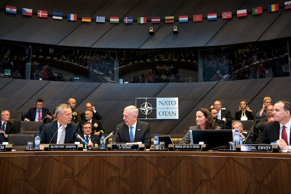 Defense Secretary James N. Mattis talks with fellow defense ministers while sitting at a table in a NATO meeting room.
