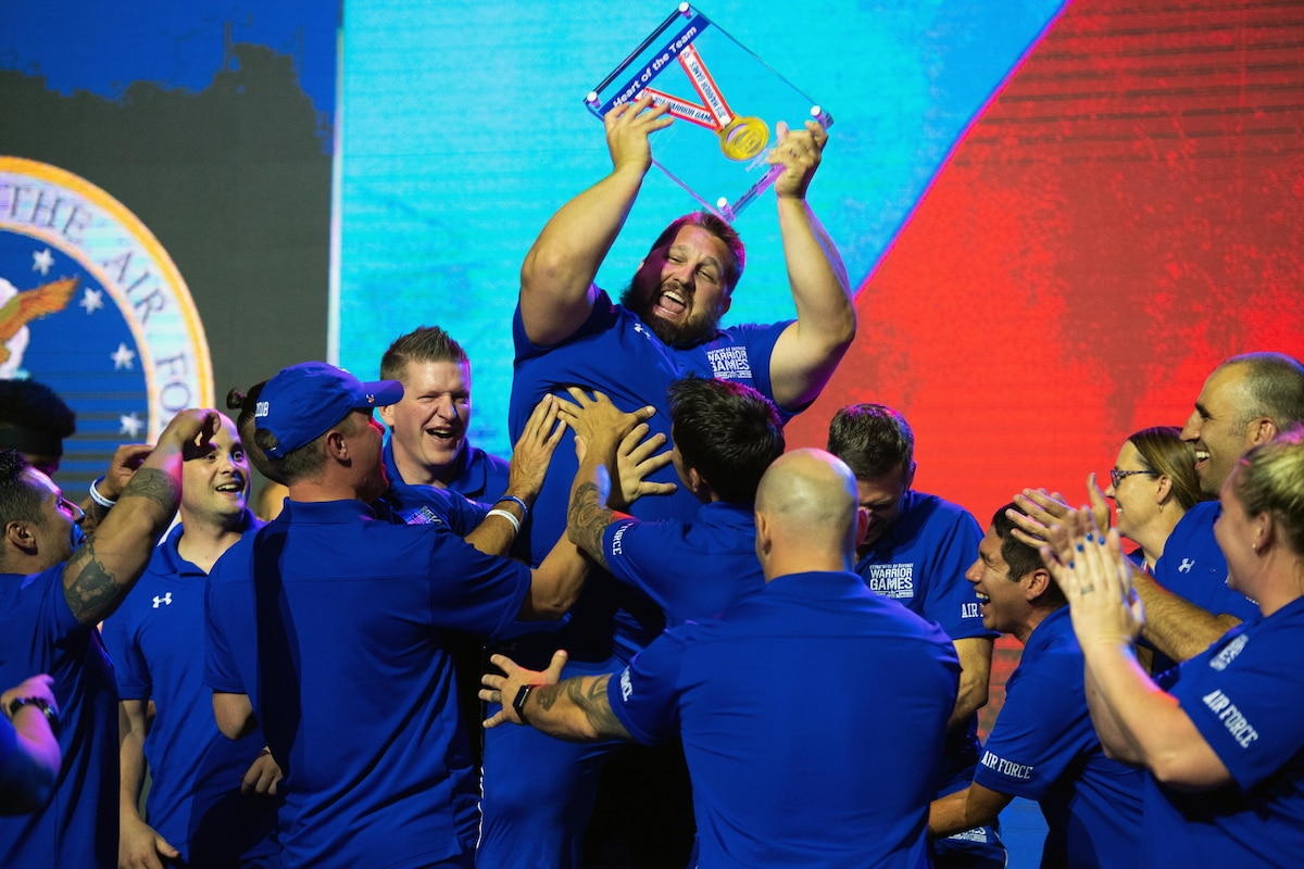 Athletes in blue uniforms hoist a teammate, who lifts a medal enclosed in glass over his head.