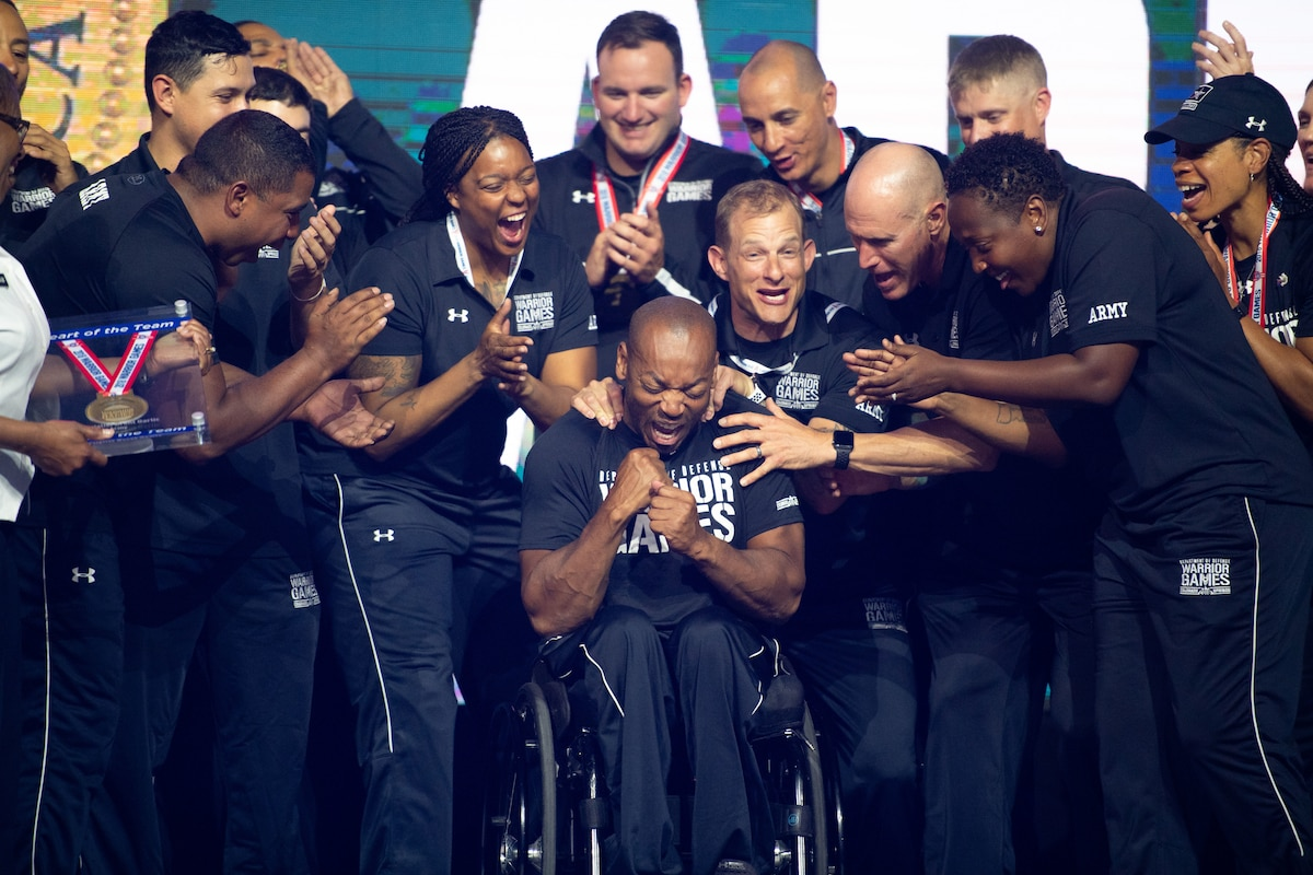 Teammates cheer for an athlete seated in a wheelchair while gathered around him.