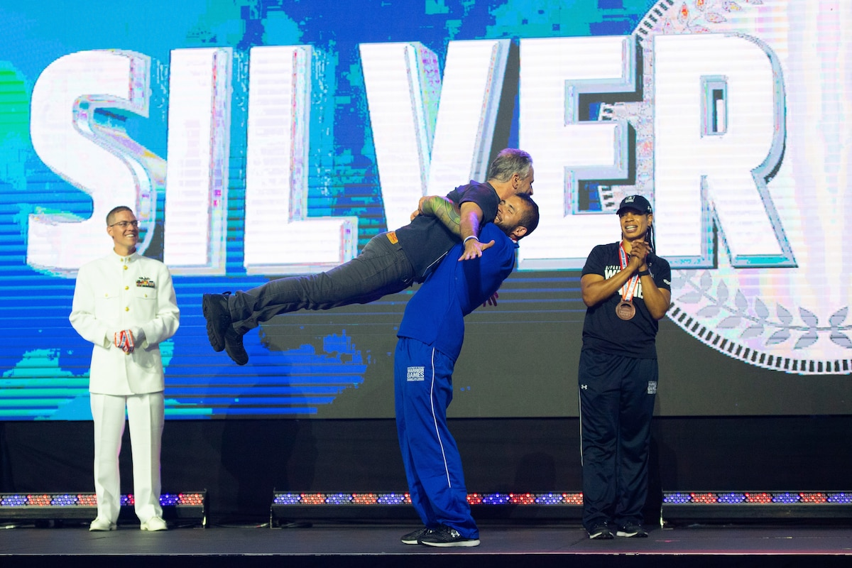 An athlete lifts comedian Jon Stewart off his feet, as two others watch and applaud.