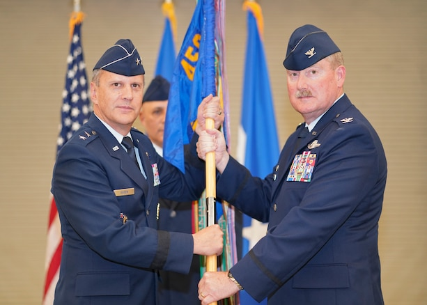 Major Gen. Randall A. Ogden, Commander, 4th Air Force, Air Force Reserve Command, March Air Reserve Base, California (left), hands the 459th Air Refueling Wing guidon to Col. Douglas E. Gullion (right) in a hangar on the Joint Base Andrews, Maryland, flight line June 9, 2018. Douglas assumes command from Col. (ret.) David A. Owens and comes to the 459th from the 507th Air Refueling Wing, Tinker Air Force Base, Oklahoma, where he served as the commander. He is a command pilot with more than 6,500 military flying hours. (U.S. Air Force photo by Tech. Sgt. Brent Skeen)