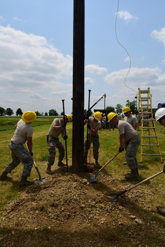 Airmen with the 211th Engineering Installation Squadron, Fort Indiantown Gap, Pennsylvania, bury a telephone pole in order to secure it properly during the squadron competition June 8, 2018. Each telephone pole was 40 feet high and weighed approximately 7,000 pounds. (U.S. Air National Guard photo by Senior Airman Julia Sorber/Released)