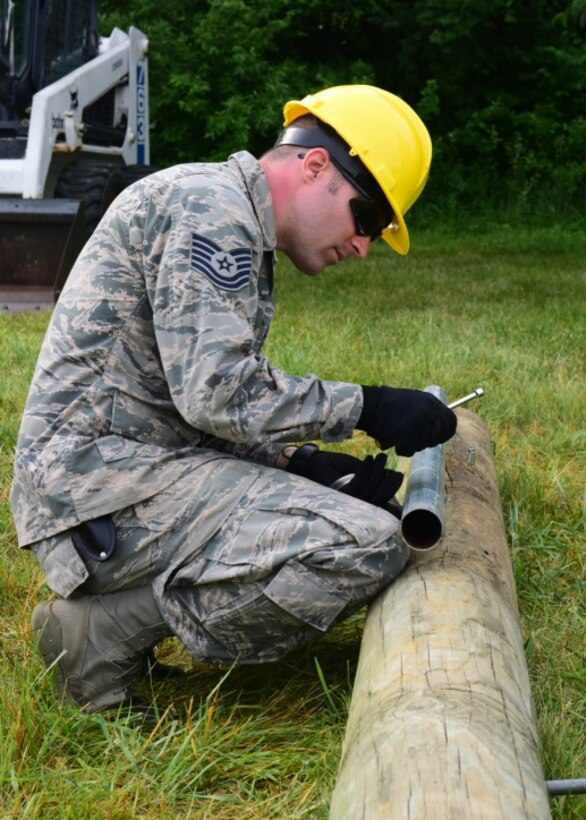 Tech. Sgt. Andrew Kindler, a cable and antenna systems specialist with the 211th Engineering Installation Squadron, Fort Indiantown Gap, Pennsylvania, install lightening protection to a telephone pole during the squadron competition June 8, 2018. Lightening protection is required so a lightning surge goes into the ground and doesn't interfere with the local area network. (U.S. Air National Guard photo by Senior Airman Julia Sorber/Released)