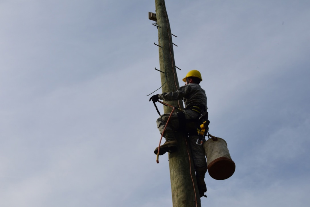 Staff Sgt. Jeremy Newton, an installations technician with the 211th Engineer Installation Squadron, Fort Indiantown Gap, Pennsylvania, climbs a telephone pole during the squadron competition June 9, 2018. Newton carried cables up the pole to attach in order to establish a connection. (U.S. Air National Guard photo by Senior Airman Julia Sorber/Released)