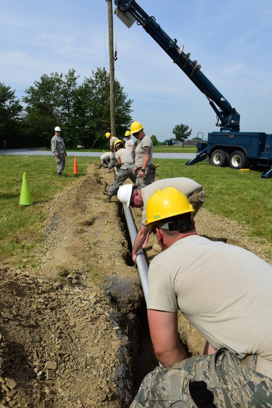 Airmen with the 211th Engineering Installation Squadron, Fort Indiantown Gap, Pennsylvania, lower a pipe into a trench during the squadron competition June 9, 2018. The pipe contained wiring that led from the shelter to the telephone pole. (U.S. Air National Guard photo by Senior Airman Julia Sorber/Released)