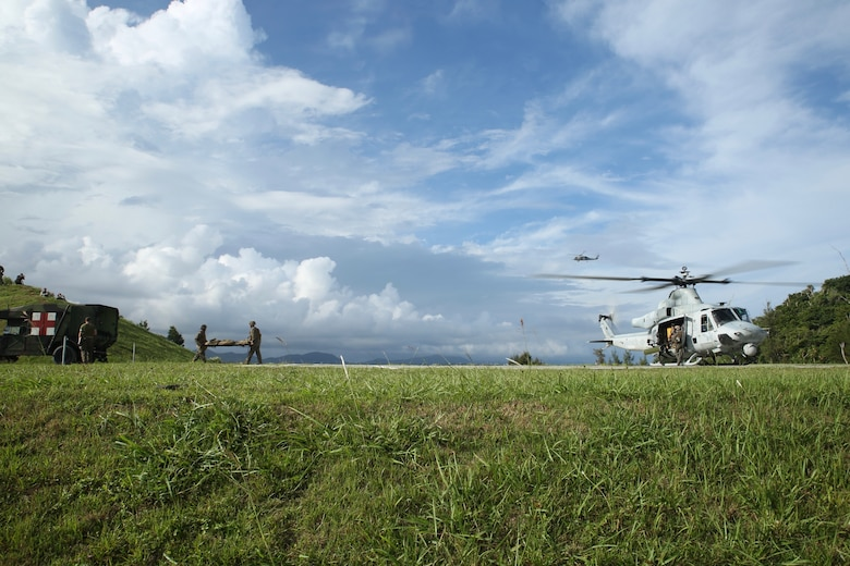 Marines with 3rd Medical Battalion, 3rd Marine Logistics Group transport a simulated casualty from a UH-1Y Venom helicopter at Landing Zone Swan on Okinawa, Japan, June 6, 2018. The simulation is part of Inochi No Onjin, an exercise utilized to validate command standard operating procedures, tactics, and techniques. The multitude of patient evacuations through the joint services increase competency of medical units' command and control abilities, medical regulating, and role-two capabilities. (U.S. Marine Corps photo by Lance Cpl. Harrison Rakhshani)