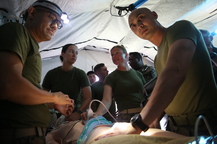 Navy field medical corpsmen with 3rd Medical Battalion, 3rd Marine Logistics Group provide emergency care to a dummy at Kin Blue on Okinawa, Japan, June 6, 2018. The simulation is part of Exercise Inochi No Onjin, which increased competency of patient evacuation, command and control medical regulating, and role-two capabilities in a joint environment.  3rd Medical Battalion is responsible for providing direct and general health service support to III Marine Expeditionary Force. (U.S. Marine Corps photo by Lance Cpl. Harrison Rakhshani)