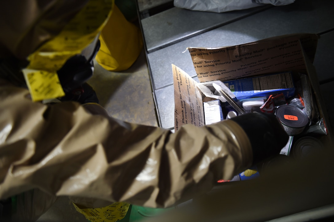 airman in protective suit scoops up powder