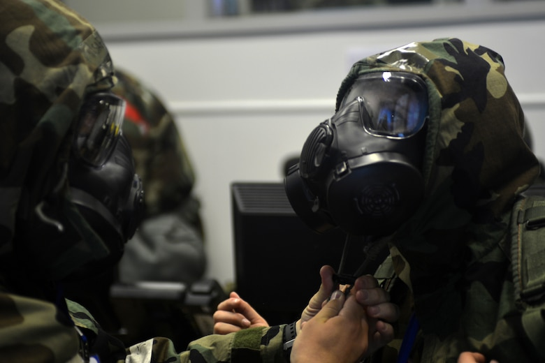 48th Fighter Wing Airmen don mission-oriented protective posture gear during a readiness exercise at Royal Air Force Lakenheath, England, June 4, 2018. Exercise scenarios were designed to emphasize the importance of combat skills effectiveness training and ensure wing Airmen are fully prepared for potential contingencies. (U.S. Air Force photo by Master Sgt. Eric Burks) (Portions of this image have been obscured to protect operational security)