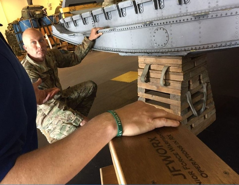The Junior Force Warfighters Operations in the Air Force Research Laboratory Materials and Manufacturing Directorate discuss replacing the old 85-pound milk stool for the C-130 aircraft with Tech. Sgt. Shawn Cooper.