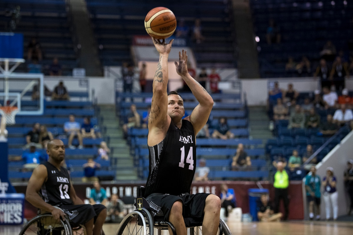 A Warrior Games athlete in a wheelchair shoots a basketball.
