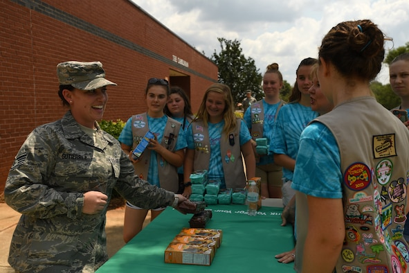U.S. Air Force Staff Sgt. Amanda Gutierrez, 145th Medical Group, picks up her favorite  box of cookies from Girl Scouts of Troop 20436, Denver, N.C., as they volunteer during the fifth annual visit to the North Carolina Air National Guard Base, Charlotte Douglas International Airport, June 9, 2018. This is part of a council-wide service project, called Operation Sweet Treat, where Girl Scouts collect cookies to give to U.S. military members serving in the United States and deployed overseas.