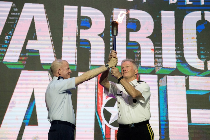 Army Gen. Raymond A. Thomas III, commander of U.S. Special Operations Command, accepts the Department of Defense Warrior Games torch from Air Force Vice Chief of Staff Gen. Stephen W. Wilson during closing ceremonies for the 2018 games at the U.S. Air Force Academy in Colorado Springs, Colo., June 9, 2018. DoD photo by EJ Hersom