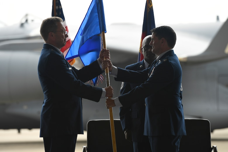 U.S. Air Force Col. Michael Gerock (right) relinquishes command of the 145th Airlift Wing (AW) and passes the guide-on to Brig. Gen. Thomas Kennett (left), Assistant Adjutant General for Air, North Carolina National Guard (NCANG), during a Change of Command Ceremony held at the NCANG Base, Charlotte Douglas International Airport, June 9, 2018. Gerock spearheaded the 145th AW transition from the C-130 Hercules aircraft to the C-17 Globemaster III aircraft during his tenure.