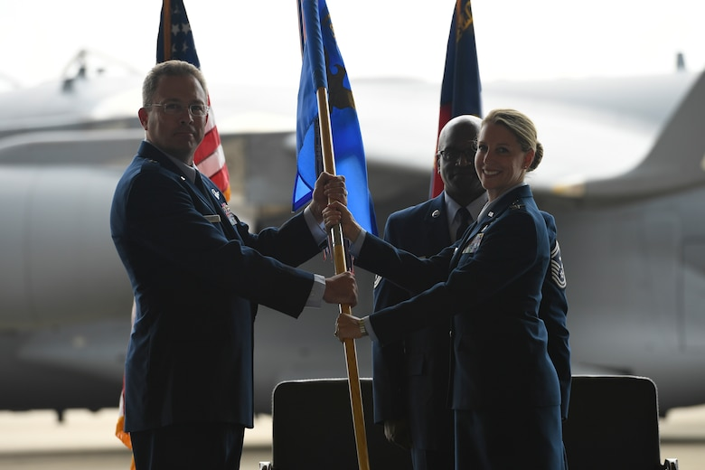 U.S. Air Force Col. Bryony Terrell, assumes command of the 145th Airlift Wing by accepting the guid-on from Brig. Gen. Thomas Kennett (left), Assistant Adjutant General for Air, North Carolina National Guard (NCANG), during a Change of Command Ceremony held at the NCANG Base, Charlotte Douglas International Airport, June 9, 2018. Terrell is the first female commander for the 145th AW and will continue the units transition to the C-17 Globemaster III.