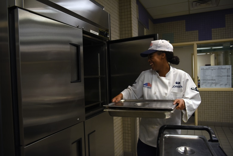 Airman Vanee Johnson, 56th Force Support Squadron services apprentice, places freshly cooked food in an oven at the Hensman Dining Facility June 7, 2018, at Luke Air Force Base, Ariz.
