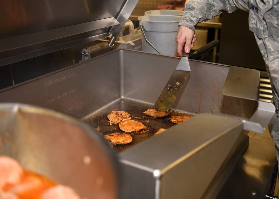 Senior Airman Jeremy Dwyer, 56th Force Support Squadron services supervisor, cooks chicken for the lunch meal at the Hensman Dining Facility June 8, 2018 at Luke Air Force Base, Ariz.