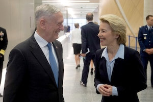 Defense Secretary James N. Mattis talks with his German counterpart in a hallway.