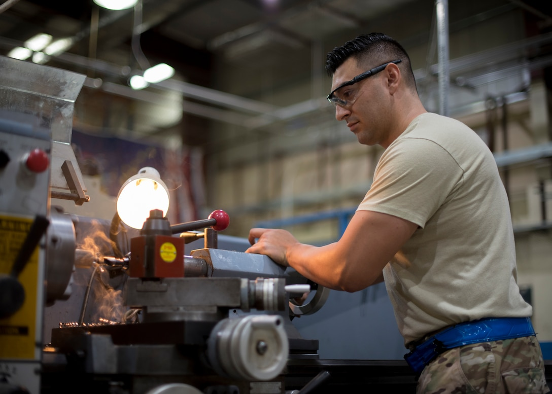 "Senior Airman Elio Esqueda, 386th Expeditionary Maintenance Squadron aircraft metals technician, uses a lathe to create a ""Spline Insert Extractor,"" May 16, 2018, at an undisclosed location in Southwest Asia. The prototype tool, originally created by Tech. Sgt. Chance Cole and Staff Sgt. Hermann Nunez, 386th Air Expeditionary Aircraft Maintenance Squadron, will save the Air Force a lot of money. (U.S. Air Force photo by Staff Sgt. Christopher Stoltz)"