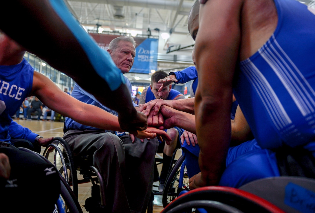 Team Air Force wheelchair basketball coach Mark Shepeherd gathers the team around before their game against Team Marine Corps during the Department of Defense Warrior Games at the U.S. Air Force Academy, Colorado Springs, Colo., June 3, 2018. Wheelchair basketball was developed by World War II U.S. veterans in 1945, and the sport was introduced on the global stage at the Rome 1960 Paralympic Games. Wheelchair basketball retains most major rules and scoring of basketball, but some rules have been modified with consideration for the wheelchair. (U.S. Air Force photo by Tech Sgt. Anthony Nelson Jr.)