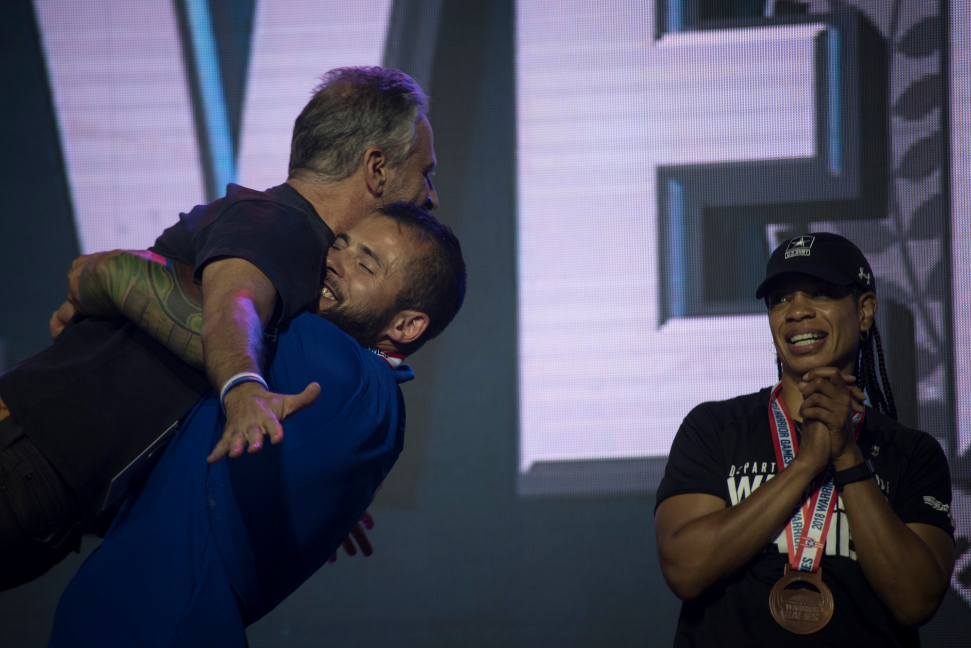 """Rafael Morfinenciso, Department of Defense Warrior Games athlete and Team Air Force member, embraces Jon Stewart, television personality and event host, after winning the """"ultimate champion"""" silver medal during the closing ceremony of the Games held at the U.S. Air Force Academy, Colorado Springs, Colo., June 9, 2018. To earn the ultimate champion title, athletes had to compete in their respective functional classifications in eight sporting events, earning points for each of their performances. The athletes with the highest cumulative points after their eight events won the bronze, silver and gold ultimate champion medals. (U.S. Air Force photo by Senior Airman Dennis Hoffman)"""