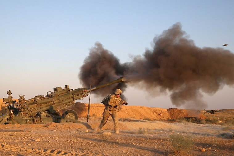 A U.S. soldiers leans away while pulling the lanyard firing artillery.