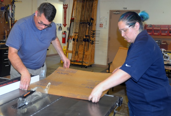 Christopher Goodrow (left) and Angelique Kelley (right), U.S. Army Medical Department Center of History and Heritage museum specialists, work on cutting and sizing a Lucite board for a new exhibit on Medal of Honor recipients who served in the U.S. Army Medical Department, or AMEDD, that will be put on display at the AMEDD Museum. Museum staff members were aiming to finish the new exhibit for public viewing by June 15.