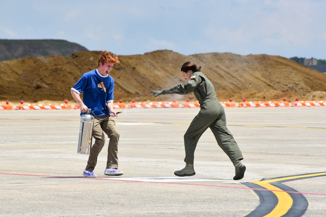 Col. Elizabeth Larson, Air Force District of Washington Operations, Plans and Requirements director, is sprayed down by her son after completing her final flight aboard the UH-1N Huey helicopter June 6.