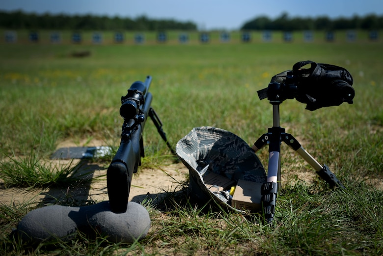 An M24 sniper weapon system, scope and hat lay on the ground.