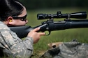 A woman in the Airman Battle Uniform and sunglasses peers down the scope of an M24 sniper weapon system.