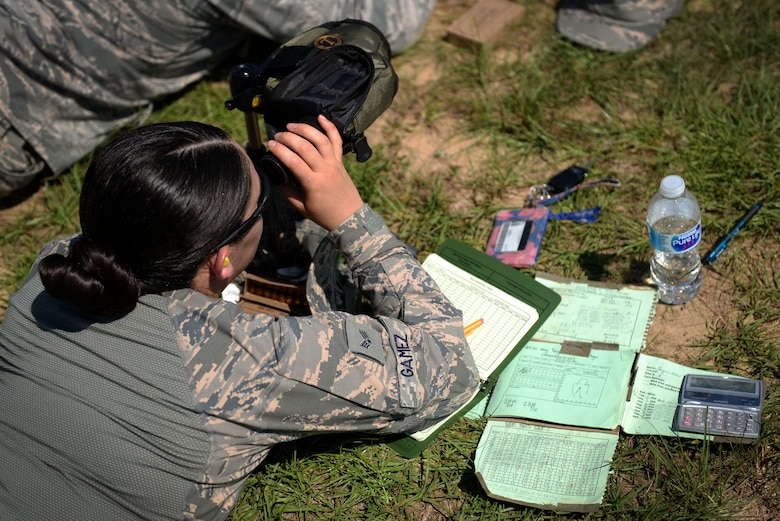 Woman in the Airman Battle Uniform looks through a scope.