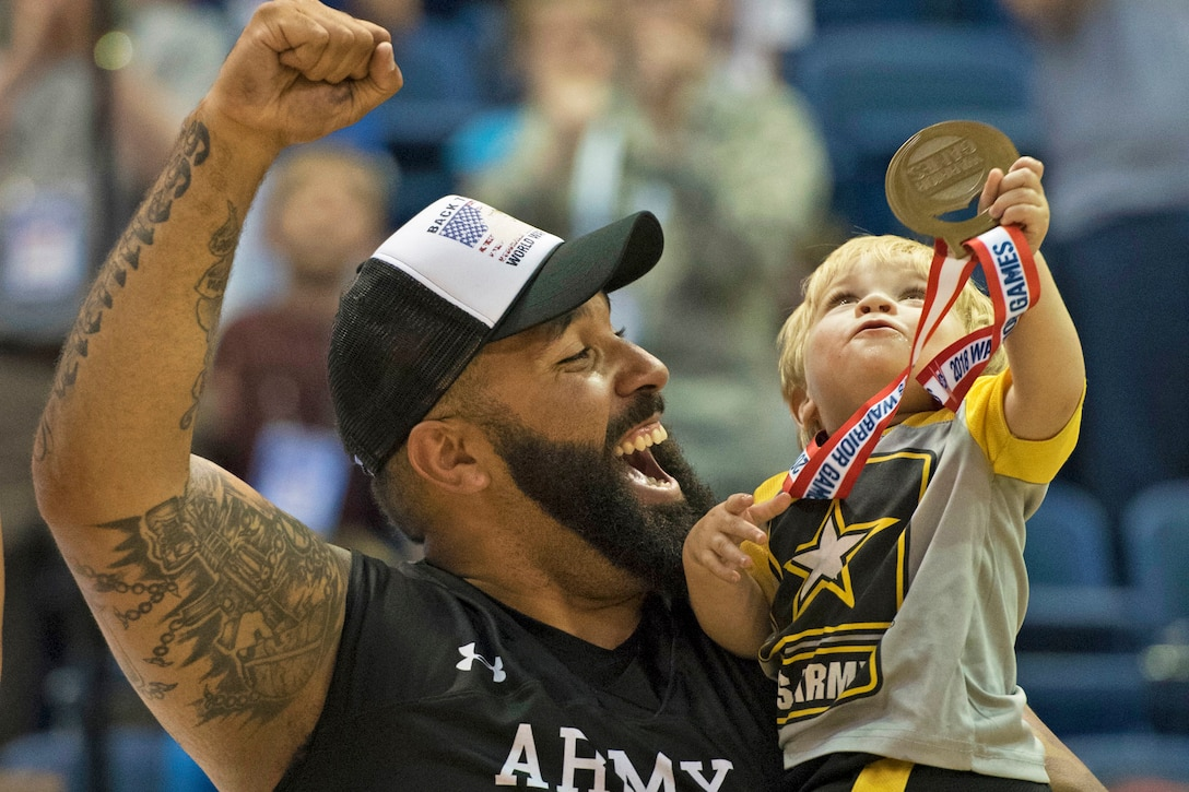 Army Sgt. Chris McGinnis and his 17-month-old son Ace celebrate Army's gold medal in wheelchair basketball.
