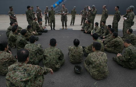 Capt. Juan Itturiaga, a supply officer with Combat Logistics Battalion 31, 31st Marine Expeditionary Unit, explains embarking procedures to Japan Ground Self-Defense Force service members during an amphibious warfare exercise at Camp Ainoura, Sasebo, Japan, May 16, 2018.