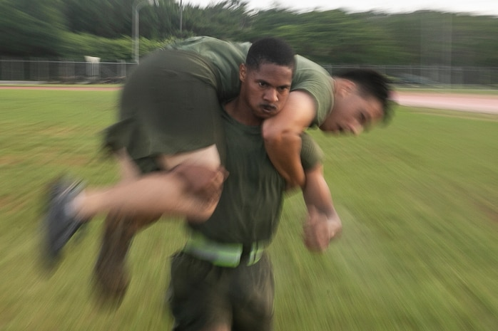 Sergeant Wesley Davison, a field radio operator with the 31st Marine Expeditionary Unit, fireman carries a fellow noncommissioned officer during a Force Fitness Instructor led High Intensity Tactical Training session at Camp Hansen, Okinawa, Japan, June 8, 2018.