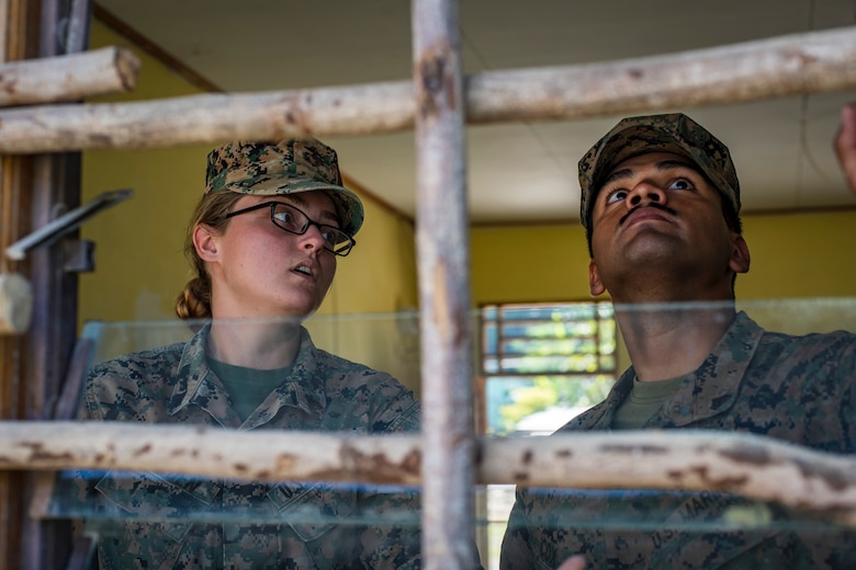 U.S. Marine Corps Cpls. Katherine Barden, left, and Lorenzo Cox, right, 7th Engineer Support Battalion combat engineers, Camp Pendleton, California, discuss their options for fixing a window during Pacific Angel 18-1, Suai, Timor-Leste, June 7, 2018.