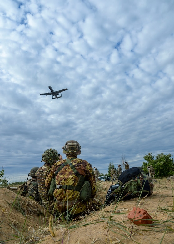 Italian Joint Terminal Attack Controllers watch an A-10 Thunderbolt II fly over Adazi, Latvia, June 7, 2018. Partner nations' controllers worked with U.S. pilots to call in air support on mock targets during Saber Strike 18. (U.S. Air Force photo by Staff Sgt. Jimmie D. Pike)
