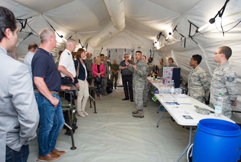 U.S. Air Force Capt. Ricardo Aldahondo, middle, 86th Medical Support Squadron Resource Management Flight commander, gives a tour of an Air Force Expeditionary Medical System (EMEDS) to host nation distinguished visitors during the 86th Medical Group's exercise Maroon Surge Community Outreach Day on Ramstein Air Base, Germany, June 7, 2018. An EMEDS is a deployable medical unit, like a tent-hospital, that is fully equipped and has rooms that can be added and removed. Ramstein welcomed visitors to tour the facilities to educate the public about Air Force capabilities, promote openness, and strengthen relations. (U.S. Air Force photo by Senior Airman Elizabeth Baker)