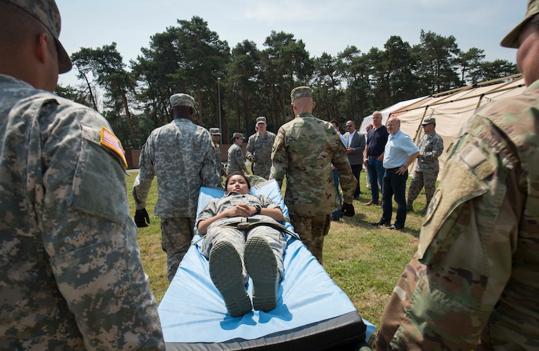 The 86th Medical Group, 345th Field Hospital, and 411th Hospital Center practice unloading a simulated patient from an ambulance during the 86th MDG's exercise Maroon Surge Community Outreach Day on Ramstein Air Base, Germany, June 7, 2018. Ramstein regularly welcomes community members to participate in tours and demonstrations to educate the public about Air Force capabilities, promote openness, and strengthen relations. (U.S. Air Force photo by Senior Airman Elizabeth Baker)