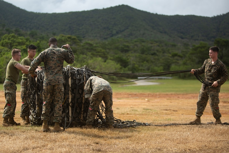 Landing support specialist Marines with Air Delivery Platoon, 3rd Transportation Support Battalion, 3rd Marine Logistics Group, participate in internal and external lift training June 6, 2018 at Landing Zone Dodo, Camp Hansen, Okinawa, Japan. Transporting cargo by aircraft provides a safe and efficient means for resupplying units in hostile environments or to deliver supplies during humanitarian crises. (U.S. Marine Corps photo by Lance Cpl. Zackary M. Walker)