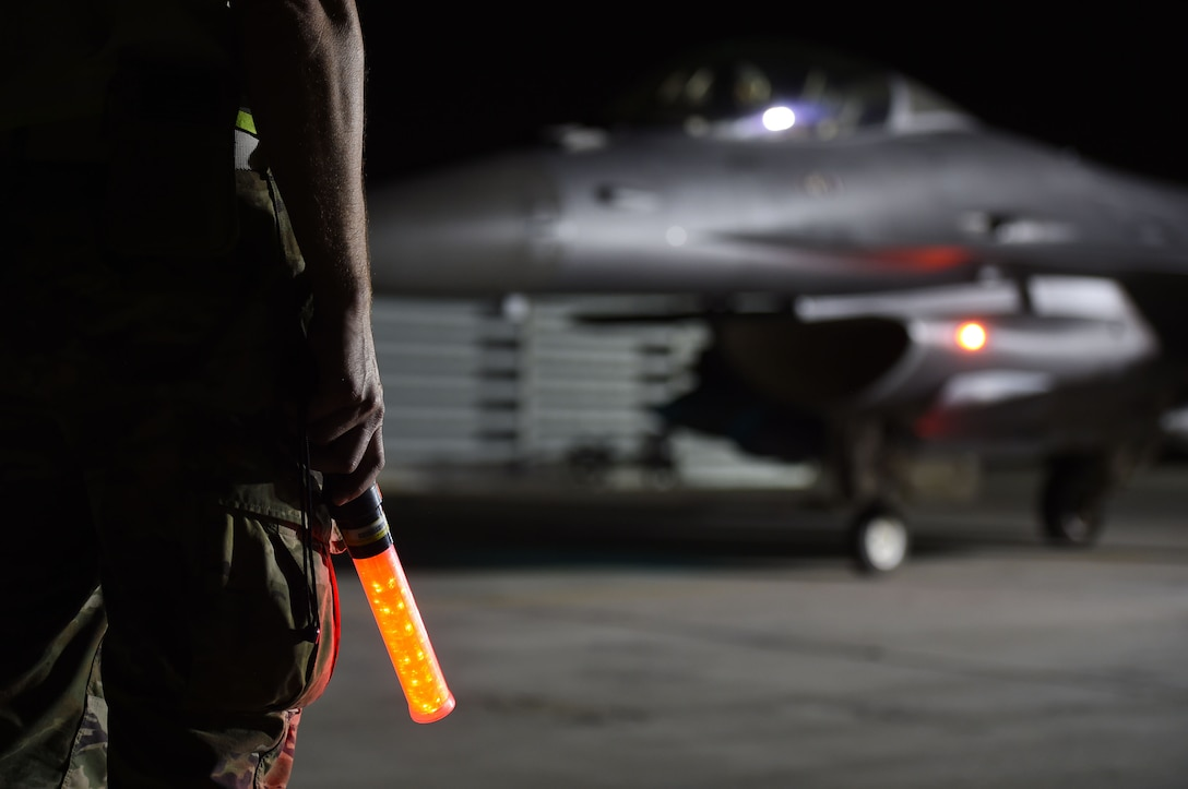 crew chief hold light in front of jet at night time.